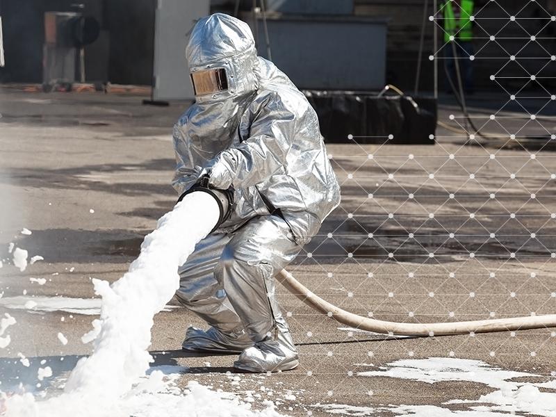 Fireman in suit using fire fighting foam